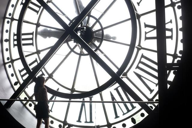 a-woman-stands-at-the-back-of-a-massive-white-clock-face.jpg