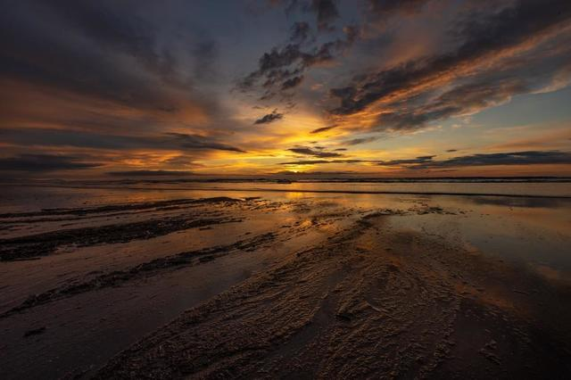 colorful-sunset-reflected-in-textured-beach-sand.jpg