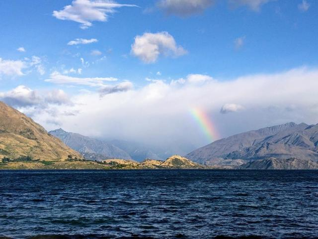 rainbow-reaches-for-clouds-by-shore.jpg